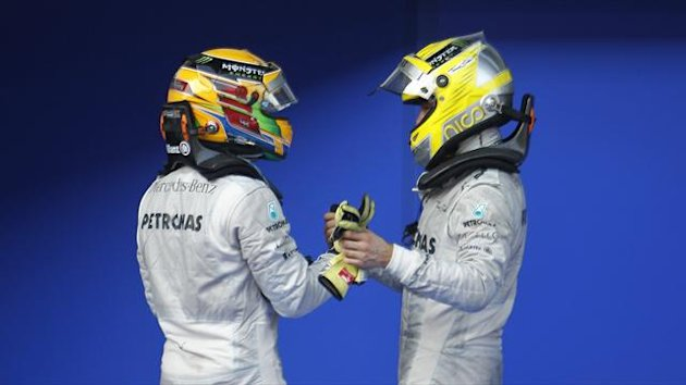 Mercedes Formula One driver Lewis Hamilton (L) of Britain and team mate Nico Rosberg of Germany congratulate each other after their 3rd and 4th respective positions during the Malaysian F1 Grand Prix (Reuters)