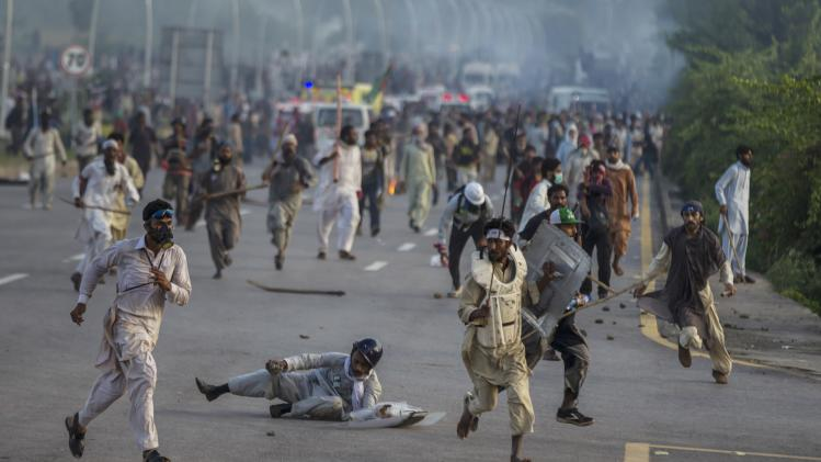 Anti-government protesters run after police personnel during the Revolution March in Islamabad