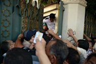 Egyptian guards try to close the gate of presidential palace to the people wanting to make personal requests to President Mohamed Morsi in Cairo. The ruling military convened an urgent meeting &quot;to discuss the presidential measures&quot; state television says