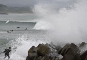 Waves crash as Typhoon Vongfong approaches Japan's main islands while surfers try to ride  a wave at Eguchihama Beach in Hioki, Kagoshima prefecture