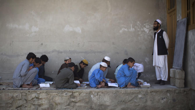 In this Tuesday, March 19, 2013 photo, Afghan boys study in a makeshift school in the village of Budyali, Nangarhar province, Afghanistan. The village lost its former school building after Taliban militants attacked the district headquarters of Budyali in July 2011. The Afghan National Army requested help from coalition forces, who responded with drones, fighter jets and rockets, leaving the school destroyed, according to village elders. (AP Photo/Anja Niedringhaus)
