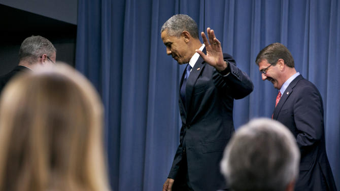 President Barack Obama waves as he leaves with Defense Secretary Ash Carter, right, after speaking to the media after receiving an update from military leaders on the campaign against the Islamic State, during a rare visit to the Pentagon on Monday, July 6, 2015. (AP Photo/Jacquelyn Martin)