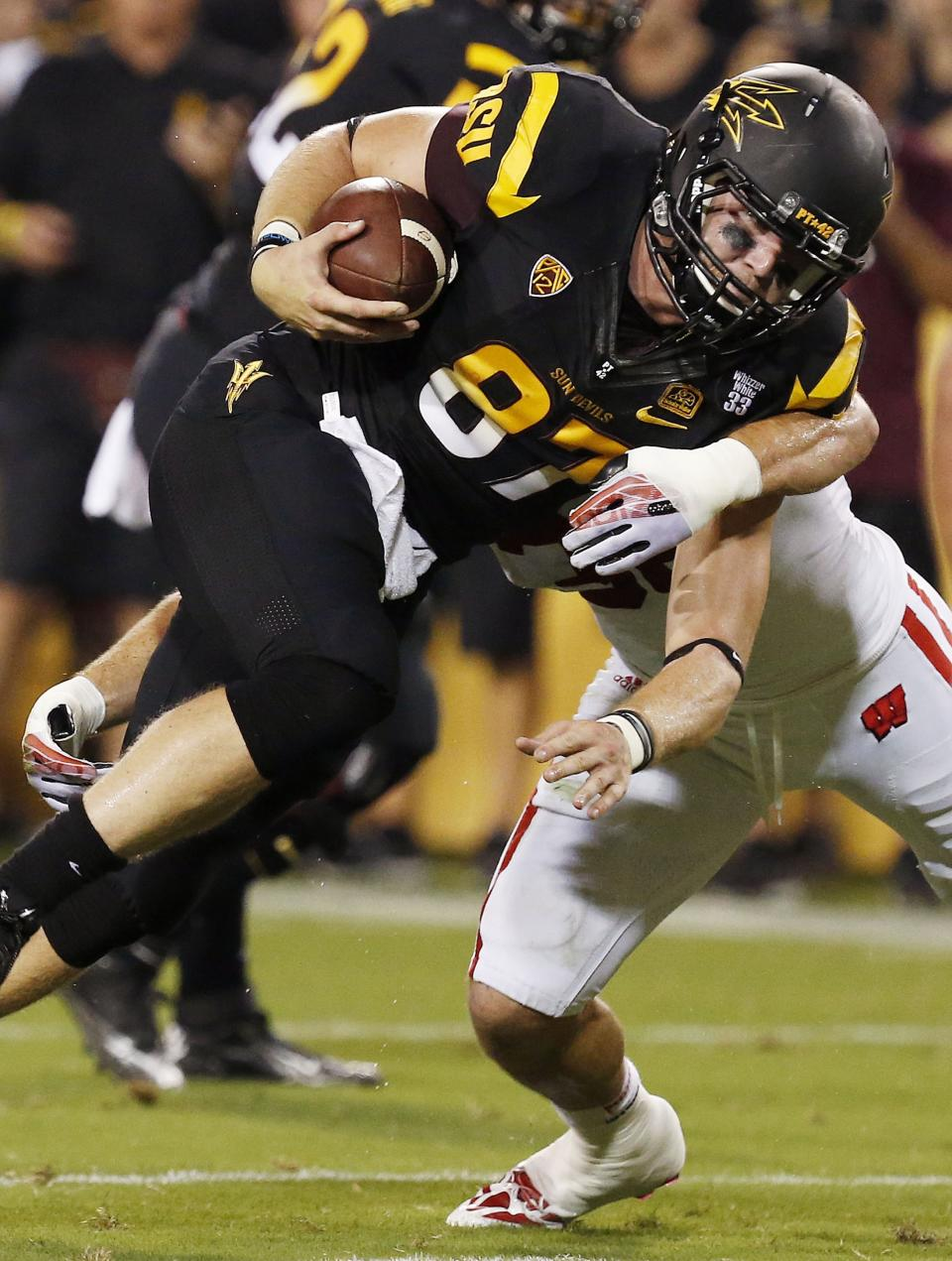Arizona State's Chris Coyle, left, breaks a tackle against Wisconsin's Ethan Armstrong in the first half of an NCAA college football game on Saturday, Sept. 14, 2013, in Phoenix. (AP Photo/Ross D. Franklin)