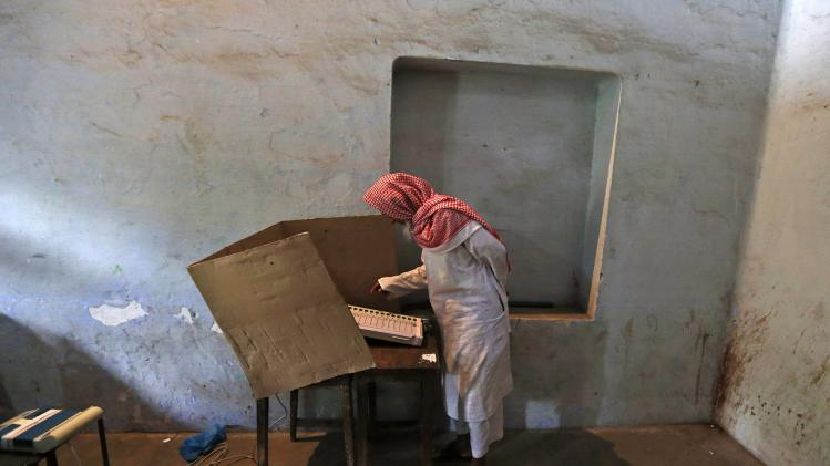 A man casts his vote inside a booth at a polling station in Shabazpur Dor village in Amroha