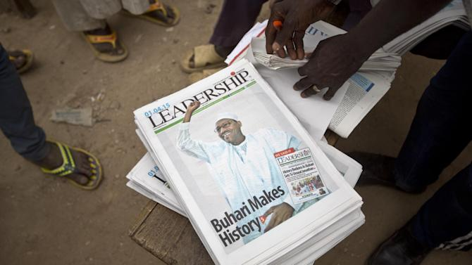 Nigerians pick up the morning's newspapers at a street stall in Kano, Nigeria Wednesday, April 1, 2015. Amid anger over an Islamic insurgency that has claimed thousands of lives, Nigerians threw out the incumbent and elected 72-year-old former military dictator former Muhammadu Buhari in a historic transfer of power officially announced early Wednesday following the nation's most hotly contested election ever. (AP Photo/Ben Curtis)