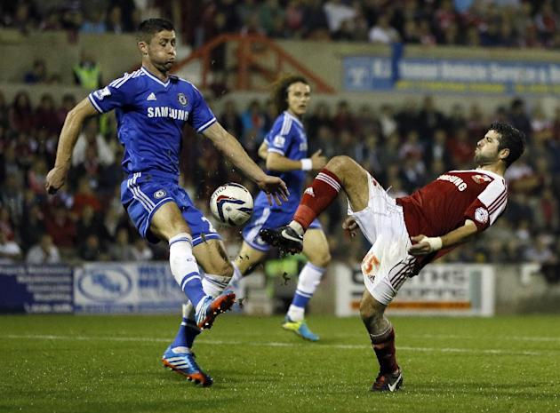 Chelsea's Gary Cahill, left, vies for the ball with Swindon's Yaser Kasim during the English League Cup soccer match between Chelsea and Swindon Town at the County Ground in Swindon, England Tuesday,