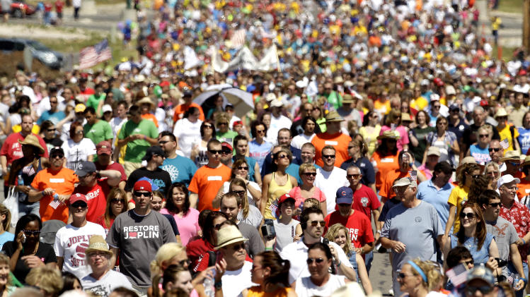 Thousands of people walk the path of destruction, Tuesday, May 22, 2012, in Joplin, Mo. The community is marking the anniversary of an EF-5 tornado that killed 161 people as it cut a wide swath through Joplin a year ago. (AP Photo/Charlie Riedel)