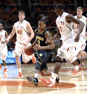 Michigan guard Trey Burke (3) splits Illinois defenders Tyler Griffey (42) and Brandon Paul (3) during the second half of an NCAA college basketball game in Champaign, Ill., on Thursday, March 1, 2012. Michigan won 72-61. (AP Photo/John Dixon)