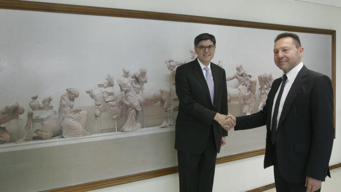 U.S. Treasury Secretary Jack Lew, left, shakes hands with Greece's Finance Minister Yannis Stournaras at the ministry in Athens, Sunday, July 21, 2013. U.S. Treasury Secretary Jack Lew has arrived in Athens to discuss Greece's efforts to overcome a deep debt crisis. Samaras is due to visit the United States in early August, where he will meet U.S. President Barack Obama. (AP Photo/John Kolesidis, Pool)