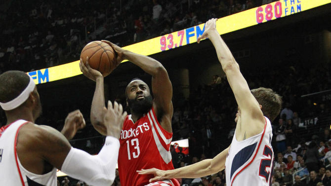 Houston Rockets shooting guard James Harden (13) puts up a shot as Atlanta Hawks shooting guard Kyle Korver, right, and Josh Smith, left, defend in the second half of an NBA basketball game on Friday, Nov. 2, 2012, in Atlanta. Houston won 109-102. (AP Photo/John Bazemore)