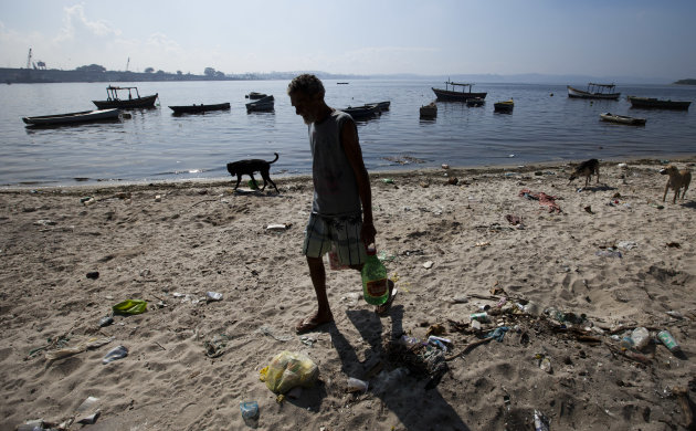 In this photo taken on Friday, June 15, 2012, a fisherman walks on a trash-ridden beach on Guanabara Bay near the international airport in Rio de Janeiro, Brazil.  The throngs streaming into Rio for t