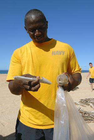 In this Thursday, Sept. 15, 2011 photo provided by the U.S. Navy, Petty Officer Jon Moore stands on the beach at Pacific Missile Range Facility, Hawaii while removing a message from a bottle sent from Kagoshima, Japan more than five years ago. Moore found the bottle while personnel at the Kauai military base and local school students picked up trash from the beach as part of International Coastal Cleanup Day. (AP Photo/U.S. Navy, Jay C. Pugh)