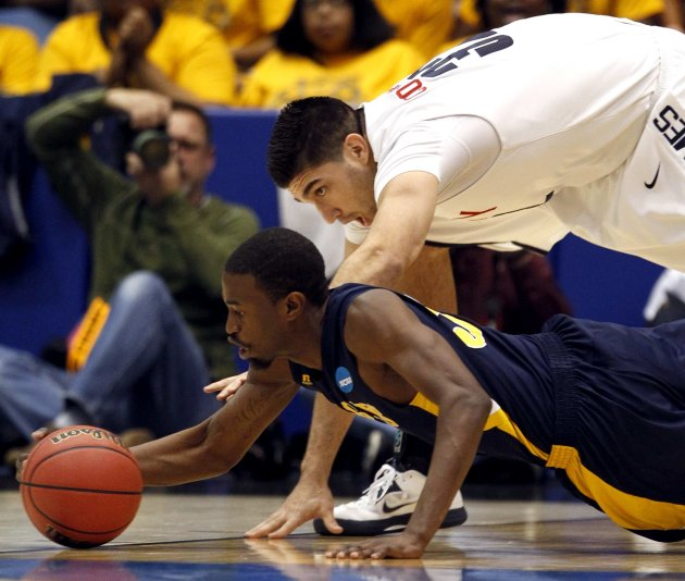 North Carolina A&T guard Jean Louisme fights for the ball with Liberty forward J.R. Coronado during the second half of their first round NCAA tournament basketball game against Liberty in Dayton