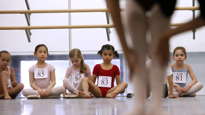 Young dancers look on as one of their peers is evaluated during an audition for six-year old ballet hopefuls at the School of American Ballet, Friday, April 5, 2013 in New York. (AP Photo/Jason DeCrow)