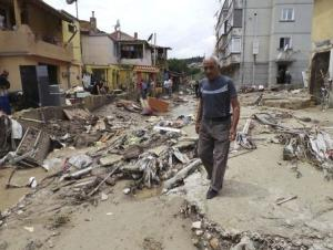 A man walks past debris on a street after heavy floods in Varna