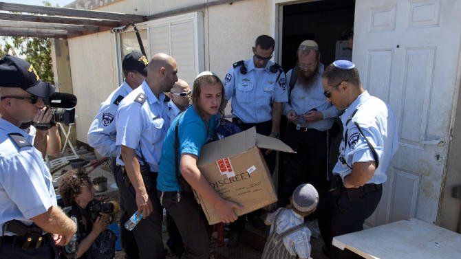 Israeli police officers stand as a Jewish settler carries a box while leaving his house in the unauthorized West Bank Jewish settlement of Migron. Sunday, Sept. 2, 2012. Israel completed evacuation of Migron, culminating years of legal wrangling in a case that has become a rallying cry for hardline settler groups opposed to any withdrawal from occupied land claimed by the Palestinians. (AP Photo/Sebastian Scheiner)