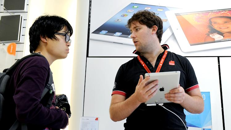A sales assistant (R) holds an Apple iPad 3 while talking to a customer at a store in Melbourne.