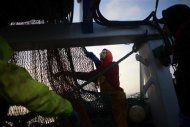 Fisherman Craig Locker unravels his fishing net aboard the Whitby Rose in the North Sea, off the coast of Whitby, northern England February 28, 2013. REUTERS/Dylan Martinez