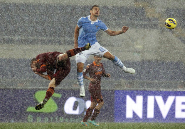AS Roma's De Rossi jumps for the ball with SS Lazio's Klose during their Italian Serie A soccer match in Rome