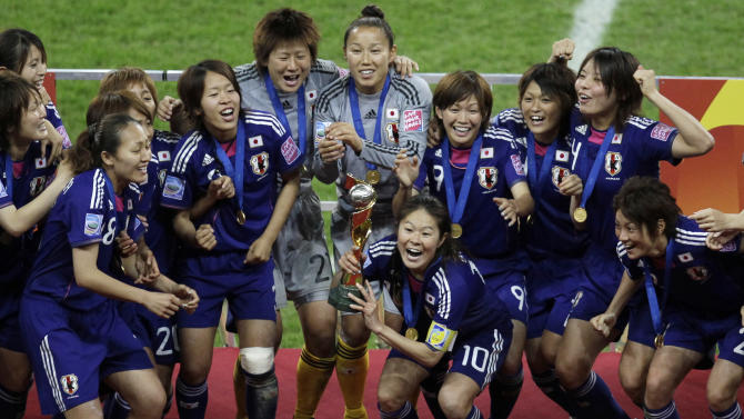 Japan's Homare Sawa holds the trophy in celebration with teammates after winnign the final match between Japan and the United States at the Women's Soccer World Cup in Frankfurt, Germany, Sunday, July 17, 2011. The Japanese women's soccer team won their first World Cup Sunday after defeating USA in a penalty shoot-out.(AP Photo/Michael Sohn)