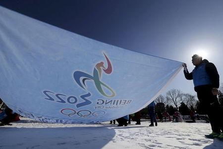 Participants hold a flag bearing the bidding logo of Beijing 2022 Winter Olympics, during a event to gather signatures to support Beijing's bid, at a park in Beijing