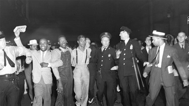 """In this July 26, 1937 file photo, police escort two of the five recently freed """"Scottsboro Boys,"""" Olen Montgomery, wearing glasses, third left, and Eugene Williams, wearing suspenders, forth left through the crowd greeting them upon their arrival at Penn Station in New York. In a final chapter to one of the most important civil rights episodes in American history, Alabama lawmakers voted Thursday, April 4, 2013, to give posthumous pardons to the """"Scottsboro Boys"""": nine black teens who were wrongly convicted of raping two white women in 1931. (AP Photo, File)"""