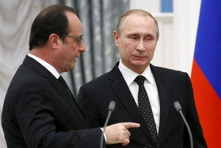 Russia's President Vladimir Putin and his French counterpart Francois Hollande speak after a news conference at the Kremlin in Moscow