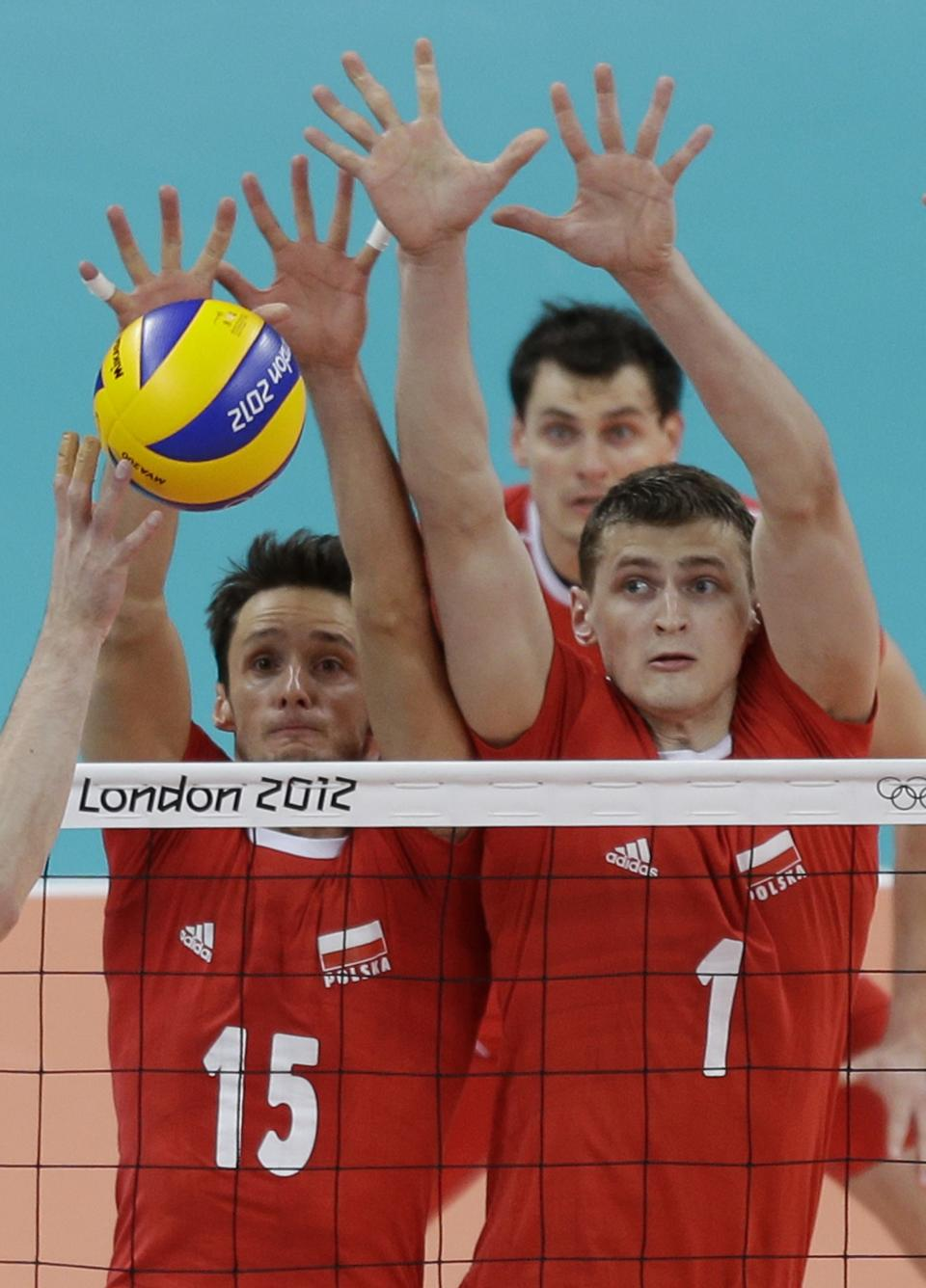 Poland's Lukasz Zygadlo (15) and Piotr Nowakowski (1) go up to block a shot by Australia's Nathan Roberts (3) during a men's volleyball preliminary match at the 2012 Summer Olympics Monday, Aug. 6, 2012, in London. (AP Photo/Chris O'Meara)