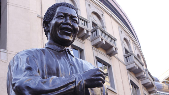 A giant statue of former president Nelson Mandela on Nelson Mandela Square in Johannesburg stands high Monday, April 1, 2013 in Johannesburg. The presidential spokesman says former president Mandela spent Monday with family members in the hospital where he is being treated for a fifth day for a recurring lung infection that developed into pneumonia. The 94-year-old who helped free South Africa from white minority rule has had weak lungs ever since he quarried stone on Robben Island during some of his 27 years of imprisonment. He contracted tuberculosis there. (AP Photo/Denis Farrell)