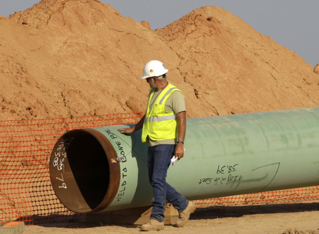 <p>               A pipeline worker walks the length of a pipe as work continues Thursday, Oct. 4, 2012, in Sumner,  Texas. Oil has long lived in harmony with farmland and cattle across the Texas landscape, a symbiosis nurtured by generations and built on an unspoken honor code that allowed agriculture to thrive while oil was extracted. (AP Photo/Tony Gutierrez)