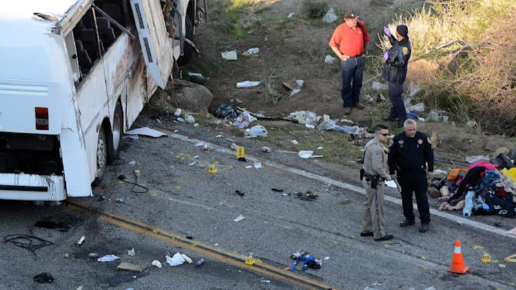Authorities work Monday Feb. 4, 2013, at the scene of Sunday's fatal tour bus crash on Highway 38 north of Yucaipa, Calif., that left at least eight people dead and dozens injured. The cause of the Sunday crash east of Los Angeles remained under investigation. (AP Photo/The Sun, Rick Sforza)