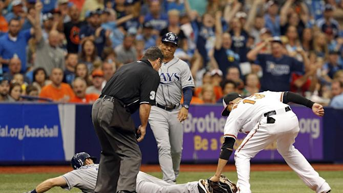 Baltimore Orioles third baseman Manny Machado, right, applies a tag to Tampa Bay Rays' Logan Forsythe who slides past third base during the fourth inning of a baseball game Sunday, May 3, 2015, in St. Petersburg, Fla. The game was moved from Baltimore to St. Petersburg due to civil unrest. (AP Photo/Mike Carlson)