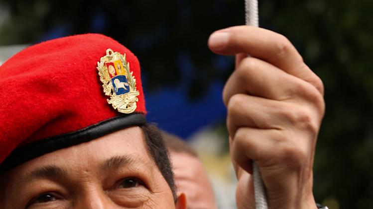 In this photo provided by Miraflores Presidential Press Office, Venezuela's President Hugo Chavez raises Venezuela's flag during a ceremony commemorating Venezuela's bicentennial in Bolivar square in Caracas, Venezuela, Thursday July 14, 2011. Ailing Chavez rallied hundreds of supporters, singing folk songs and calling cancer one of his life's greatest battles. Chavez has been limiting his public appearances since returning to Venezuela on July 4, two weeks after undergoing surgery in Cuba to remove a cancerous tumor from his pelvic region.  (AP Photo/Miraflores Presidential Office)