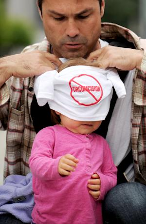 Edward Quigley dresses his daughter Phoebe Quigley, 17 months, in an anti-circumcision shirt while rallying outside a San Francisco courthouse on Thursday, July 28, 2011. A judge today struck a measure from the city's November ballot calling for a ban on male circumcision, saying the proposed law violates a law that makes regulating medical procedures a function of the state, not cities. (AP Photo/Noah Berger)