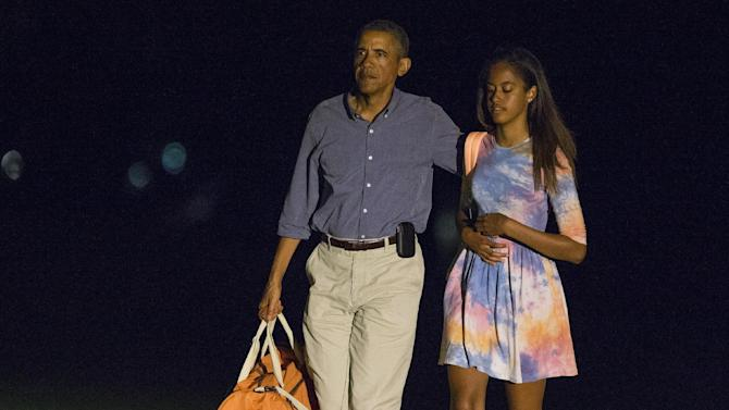President Barack Obama walks with his daughter Malia as he arrives on the South Lawn of the White House on Monday, Aug. 18, 2014, in Washington. Obama is taking a break in the middle of his Martha's Vineyard vacation to return to Washington for meetings with Vice President Joe Biden and other advisers on the U.S. military campaign in Iraq and tensions between police and protesters in Ferguson, Missouri. (AP Photo/Evan Vucci)
