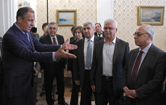 Russian Foreign Minister Sergey Lavrov, left, welcomes a delegation headed by a leader of the Syrian National Council (SNC), Abdulbaset Sieda, right, in Moscow, Russia, Wednesday, July 11, 2012. (AP Photo/Misha Japaridze)