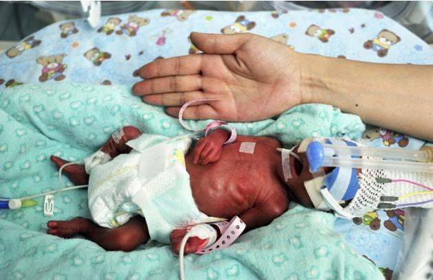 Baby boy the length of a palm is seen inside an incubator in this posed picture taken at a hospital in Xi'an