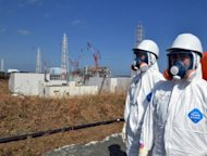 Tokyo Electric Power Co (TEPCO) workers stand before the stricken Fukushima nuclear plant on February 28. Japan&#39;s government will take a controlling stake in the operator of the Fukushima nuclear plant under a plan ministers approved Wednesday, effectively nationalising one of the world&#39;s largest utilities