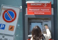 <p>A woman takes money from one Unicredit bank cash dispenser in downtown Rome. Italy raised 7.5 billion euros ($9.2 billion) euros in one-year bonds on Thursday at a sharply lower rate than in the last similar sale, the Bank of Italy said, indicating improved investor confidence.</p>