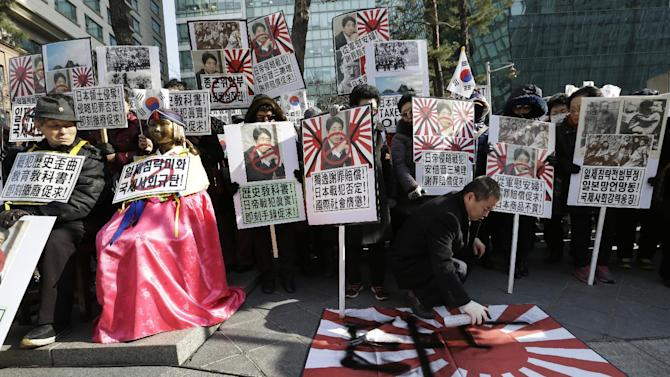 "A protester sprays to deface a Japanese rising sun flag during a rally to mark upcoming the March First Independence Movement Day, the anniversary of the 1919 uprising against Japanese colonial rule, in front of Japanese Embassy in Seoul, Friday, Feb. 27, 2015. The banners reads ""Distorted Japanese history textbooks and full compensation and apology for wartime sex slaves from Japanese government"".  (AP Photo/Ahn Young-joon)"
