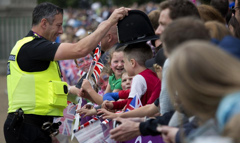In this Tuesday, Aug. 7, 2012 photo, a policeman jokes with children as they wait for men's triathlon to pass by at the 2012 Summer Olympics, in London. (AP Photo/Emilio Morenatti)
