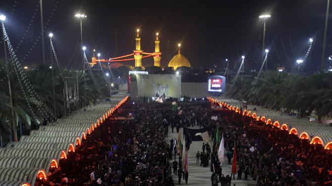Shiite Muslim worshippers gather outside Imam Hussein shrine, seen in the background, to mark the Muslim festival of Ashoura, an important period of mourning for Shiites in Karbala, 50 miles (80 kilometers) south of Baghdad, Iraq, Saturday Nov. 24, 2012. The festival of Ashoura commemorates the martyrdom of Imam Hussein, the grandson of Prophet Muhammad at the Battle of Karbala, Iraq, in the year A.D. 680. (AP Photo / Khalid Mohammed)