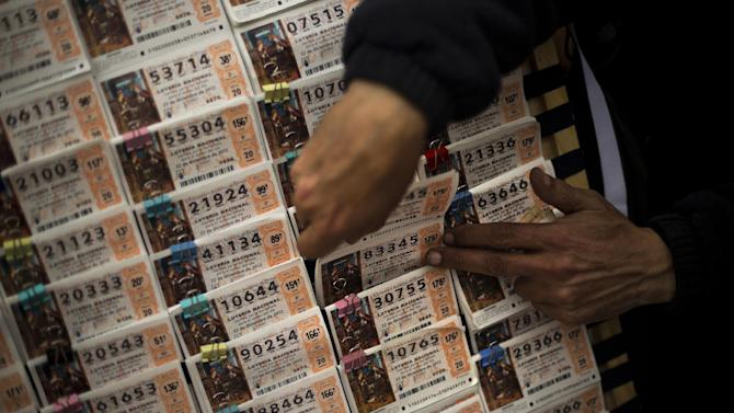 """A seller grabs tickets for the famed Christmas lottery, in Madrid, Friday, Dec. 21, 2012.   Known as """"El Gordo"""" (The Fat One) and billed as the world's richest lottery, the drawing will hand out about 2.5 billion of euros (US dlrs 3.3 billion) on upcoming Saturday. The top prize is about 400,000 euros (US dlrs 530,000) but there are expected to be hundreds or thousands of tickets awarded for that amount. (AP Photo/Daniel Ochoa de Olza)"""