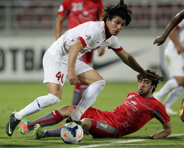 Khaled Muftah of Qatar's Lekhwiya fights for the ball with Saeid Daghighi of Iran's Tractor Sazi FC during their AFC Champions League soccer match in Doha