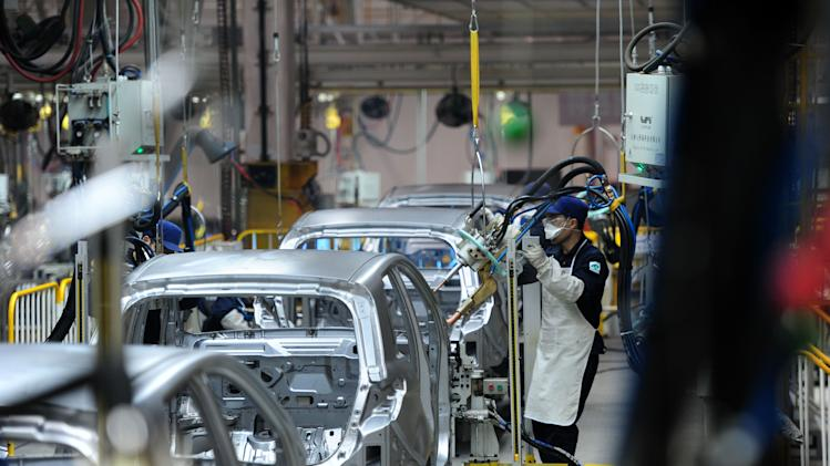 FILE - In this March 6, 2012 file photo, workers assemble cars at the factory of BAIC Motor Corporation in Zhuzhou in south China's Hunan province. Plagued by uncertainty and fresh setbacks, the world economy has weakened further and will grow more slowly over the next year, the International Monetary Fund says in its latest forecast. Advanced economies are risking recession, the international lending organization said Monday, Oct. 9 in a quarterly update of its World Economic Outlook, and the malaise is spreading to more dynamic emerging economies such as China. (AP Photo/File) CHINA OUT