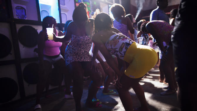 "In this Feb. 3, 2012 photo, women dance during a funk ""baile"" in the Cantagalo slum in Rio de Janeiro, Brazil. Huge funk ""bailes,"" or parties, go on past dawn, packed with shirtless young men who can be heavily armed drug dealers, in slums far from police control. Subgenres can glorify the lifestyle of drug dealers, much like Mexico's narco-corridos, or simply serve as a titillating escape from the workaday grind. (AP Photo/Felipe Dana)"