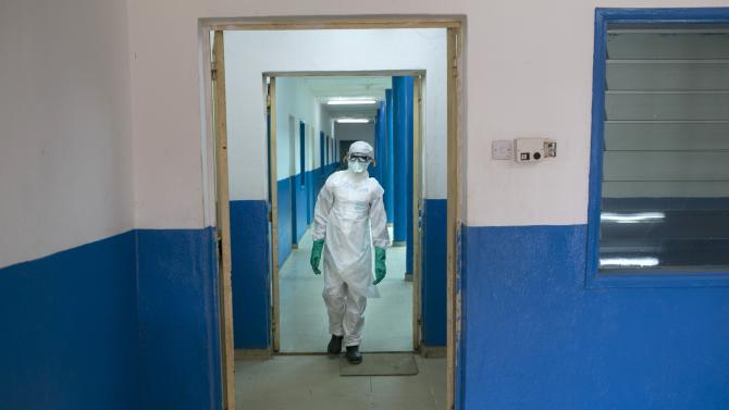 A health worker in protective gear walks inside a Red Cross facility in the town of Koidu