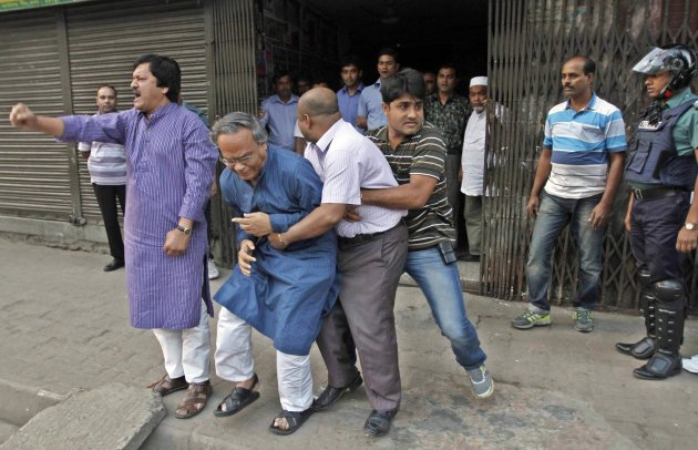 A plain-clothed police officer attempts to arrest activists from the Bangladesh Nationalist Party in front of their office during a country-wide strike in Dhaka