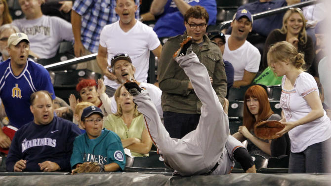Fans look on as Baltimore Orioles first baseman Mark Reynolds dives into the stands to snag a foul ball from Seattle Mariners' Jesus Montero to end the first inning of a baseball game, Monday, Sept. 17, 2012, in Seattle. (AP Photo/Elaine Thompson)
