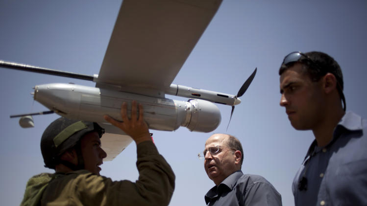 "File - In this July 9, 2013 file photo, an Israeli soldier holds up a Skylark I (Rochev Shamayim) unmanned drone as part of a demonstration for Israel's Defense Minister Moshe Yaalon, center, in an urban warfare army training facility, near Zeelim, southern Israel. Israel's defense minister was quoted Tuesday as deriding U.S. Secretary of State John Kerry's Mideast peace efforts as naive and foolhardy, triggering an angry response from Washington and rekindling simmering tensions with Israel's closest and most important ally. In the comments published by the Yediot Ahronot daily, Defense Minister Moshe Yaalon called Kerry ""obsessive"" and ""messianic"" and dismissed Kerry's security plan as worthless. ""The only thing that might save us is if John Kerry wins the Nobel Prize and leaves us be,"" Yaalon was quoted as saying in private conversations. (AP Photo/Ariel Schalit, File)"